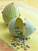 Sugar eggs falling out of large paper Easter egg