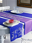 Blue and purple table runners, crockery and glasses