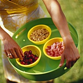 Woman holding tray of cherries, jelly sweets and peanuts