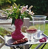 Vase of lilies and fresh fruit on table out of doors