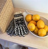 Mandarin oranges in bowl beside winter gloves