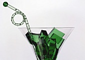 Green jelly cubes (woodruff jelly) in a glass
