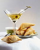 Filled filo pastry triangles & a glass of Martini with olive