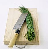 A bunch of chives with knife on wooden board