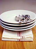 Pile of plates with spoons