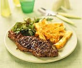 Peppered steak with strips of bread and salad