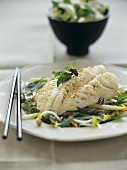Steamed perch with sesame on bed of vegetables and sprouts