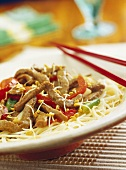 Strips of beef with sprouts and spaghetti
