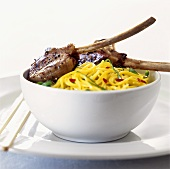 Lamb cutlets on yellow noodles