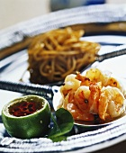 Shrimps and noodles on ladle and chili sauce in lime