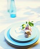 Two garlic bulbs on pale-blue plates