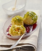 Apricot dumplings with pistachios on cranberry sauce