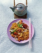 Pan-cooked chicken dish with nuts and fried noodles