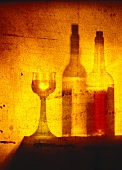 White wine glass, white and red wine bottles behind canvas
