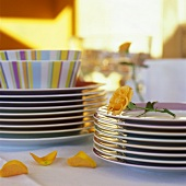 Pile of plates with a rose on buffet