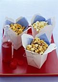 Popcorn in Take-Out-Behältern und eine Flasche Cranberrysaft