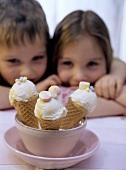 Three ice cream cones, a girl and a boy behind