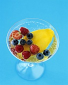 Champagne cocktail with mango and berries