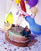 Birthday cake with three candles and balloons