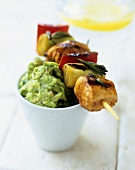 Salmon and vegetable kebab on guacamole