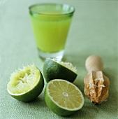 Lime halves, wooden citrus squeezer and lime juice