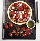Pizza with whole tomatoes, olives and sheep's cheese