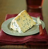 A piece of Stilton cheese with knife