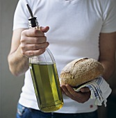 Man holding a bottle of olive oil and a loaf of bread