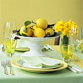 Bowl of lemons on table laid for two