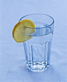 Ein Glas Wasser mit einer Zitronenscheibe