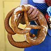 Woman holding two large pretzels in her hand