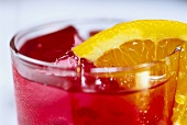Campari with slice of orange and ice cubes