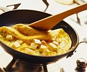 Ein Omelett wird in der Pfanne umgedreht