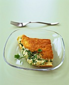 Half an omelette with cheese and onion filling and herbs