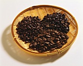 Three types of coffee beans on wicker tray