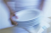 Hands holding a pile of plates