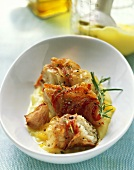 Cod wrapped in pancetta on a bed of mashed potato with orange