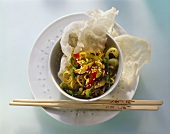 Vegetables, sesame & noodles in small bowl with prawn crackers