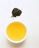 Bowl of green tea and green tea leaves