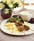 Cevapcici on sticks on couscous