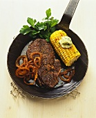 Beef steak with onion rings and corncob in frying pan