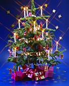 Decorated Christmas tree with candles and gifts