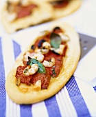 Mini-pizza with tomatoes, shrimps and basil