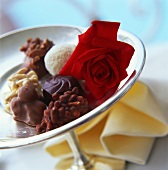 Assorted chocolates and red rose on silver plate