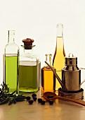 Various types of olive oil in bottles; olive branch; olives
