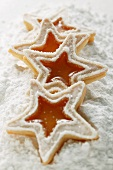 Star-shaped butter biscuits (jam biscuits) on icing sugar