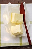 Two cubes of butter in butter paper with wooden spoon