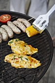 Chicken, corncob and sausages on a barbecue