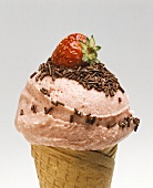 Strawberry ice cream with chocolate sprinkles in a cone
