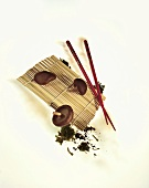 Still life with shiitake mushrooms, bamboo mat & chopsticks